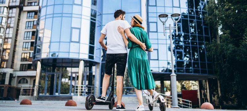 Homme et femme en trottinette électrique de ville
